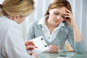 Красивая девушка, которой плохо, сидит напротив врача, записывающего на бумаге_медпросвіта