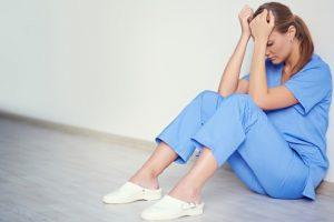 медсестра сидит на полу прижимая руки к голове, медпросвіта